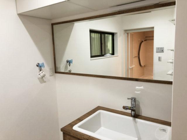 横長の洗面鏡で空間を広く見せる。